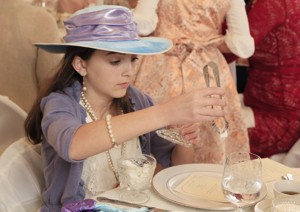 Photo -  Maycie Andress, 10, places sugar in her tea during the fifth annual Victorian Tea. [PHOTO BY PAUL HELLSTERN, THE OKLAHOMAN]