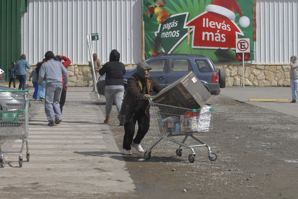"A man runs away carrying electronic goods and packages containing food during looting at a supermarket in San Carlos de Bariloche, about 1.630 km southwest of Buenos Aires, Argentina, Thursday, Dec. 20, 2012. Hooded people looted at least three supermarkets and set a car on fire after claiming for food to celebrate Christmas in the city of Bariloche, part of Argentina's Patagonia region. The sign in background reads in Spanish ""pay less, take more."" (AP Photo/Diario Rio Negro)"