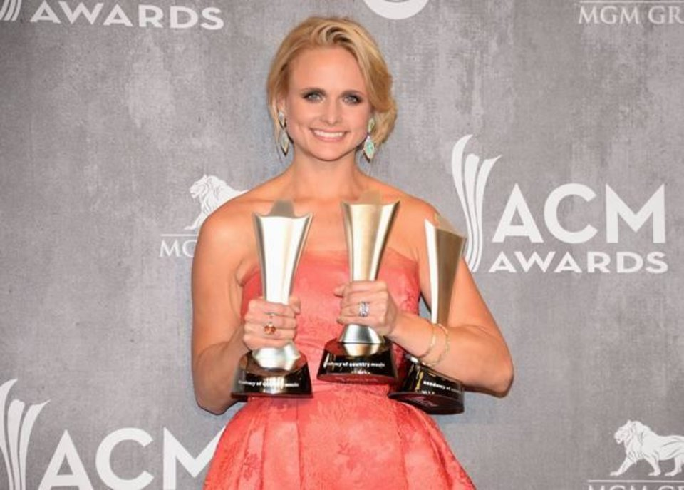 Photo -  Miranda Lambert poses in the press room with the awards for vocal event of the year, female vocalist of the year and single record of the year at the 49th annual Academy of Country Music Awards at the MGM Grand Garden Arena on Sunday, April 6, 2014, in Las Vegas. (AP)