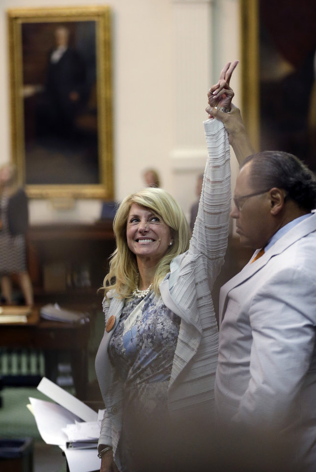Photo - Sen. Wendy Davis, D-Fort Worth, left, who tries to  filibuster an abortion bill, reacts as time expires, Tuesday, June 25, 2013, in Austin, Texas. Amid the deafening roar of abortion rights supporters, Texas Republicans huddled around the Senate podium to pass new abortion restrictions, but whether the vote was cast before or after midnight is in dispute. If signed into law, the measures would close almost every abortion clinic in Texas.  (AP Photo/Eric Gay)