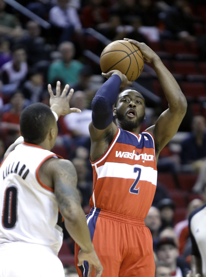 Photo - Washington Wizards guard John Wall, right, shoots over Portland Trail Blazers guard Damian Lillard during the first half of an NBA basketball game in Portland, Ore., Thursday, March 20, 2014. (AP Photo/Don Ryan)