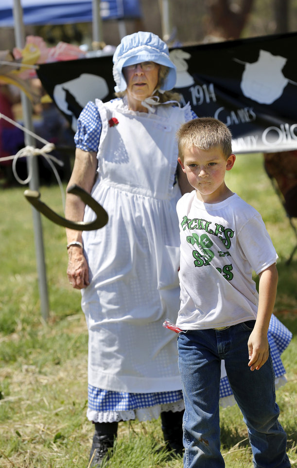"Photo - Volunteer Joyce Stockton stands behind Josh Ayers, 7, from Antlers, Okla., as they both watch to see where his horse shoe lands.  Stockton is with women from Grady County Rural Neighbors, Oklahoma Home and Community Education Group, in Chickasha, who hosted a tent where children could play ""non-electronic"" games typical of ones played by young people in the early 1900s.  Children were able to compete in sack races, toss horseshoes, play jacks, jump rope,  and engage in other assorted fun physical activities.  Oklahoma Cooperative Extension Service celebrated their 100th anniversary with a Whistle Stop and Festival on Saturday, April, 12, 2014 at the Rock 'N Rail yard near Highway 66 in Wellston, Oklahoma.  ""In the early 1900s, trains were the modern way to travel and early Extension agents were allowed to 'ride the rails', going from town to town presenting demonstrations  and showing people how they might improve the quality of their lives by making use of the latest science-proven advances, practices and products,"" said James Trapp. OCES associate director. A train coming into town was sometimes referred to  as a ""county fair on wheels."" As part of its centennial celebration, Extension conducted an historic reenactment  of the type of whistle stop tours that would have occurred   in 1914. Visitors  at the festival were given the opportunity to visit a variety of tents and booths offering demonstrations and hands-on activities representative of Extension programs. Photo by Jim Beckel, The Oklahoman"
