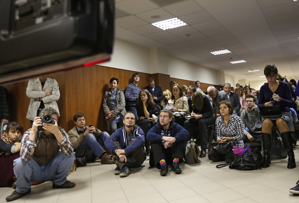 Photo -   Media watch a TV screen in a hall outside a court room of the Moscow City Court where three members of the punk band Pussy Riot are set to make their case before a Russian appeals court that they should not be imprisoned, in Moscow, Wednesday. Oct. 10, 2012. Their impromptu performance inside Moscow's main cathedral in February came shortly before Putin was elected to a third term. The three women were convicted in August of hooliganism motivated by religious hatred and sentenced to two years in prison. (AP Photo/Sergey Ponomarev)
