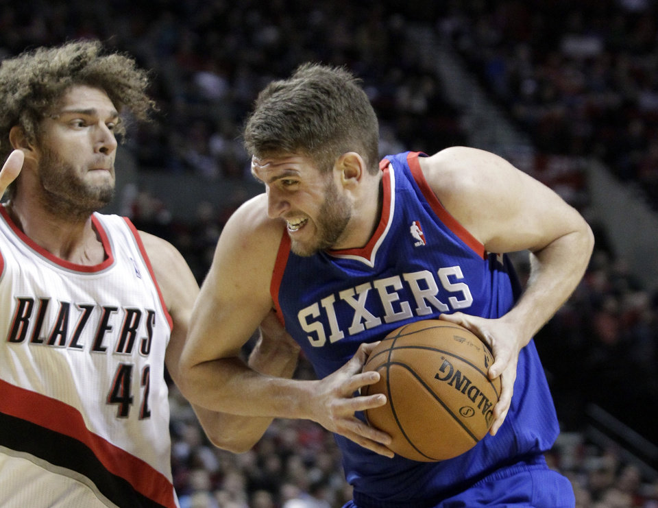 Photo - Philadelphia 76ers center Spencer Hawes, right, drives to the basket against Portland Trails Blazers center Robin Lopez during the first half of an NBA basketball game in Portland, Ore., Saturday, Jan. 4, 2014. (AP Photo/Don Ryan)