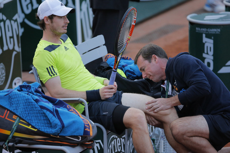 Photo - Britain's Andy Murray is treated for a left leg injury during the third round match of the French Open tennis tournament against Germany's Philipp Kohlschreiber at the Roland Garros stadium, in Paris, France, Saturday, May 31, 2014. The match was suspended in the fifth set because of the onset of darkness. (AP Photo/Michel Spingler)