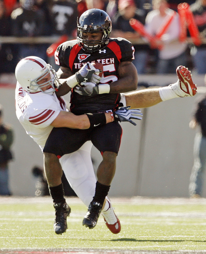 Photo - OU's Ryan Reynolds (4) tackles Baron Batch (25) of Texas Tech during the college football game between the University of Oklahoma Sooners (OU) and the Texas Tech University Red Raiders (TTU) at Jones AT&T Stadium in Lubbock, Texas, Saturday, Nov. 21, 2009. Photo by Nate Billings, The Oklahoman