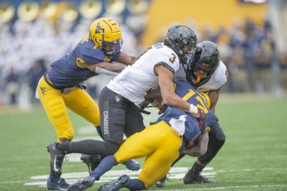 Photo -  Oklahoma State safety Tre Sterling (3) helps tackle West Virginia receiver Sam Jones (13) during the Cowboys' 20-13 win Saturday at Milan Puskar Stadium in Morgantown, W.Va. [Bruce Waterfield/OSU Athletics]