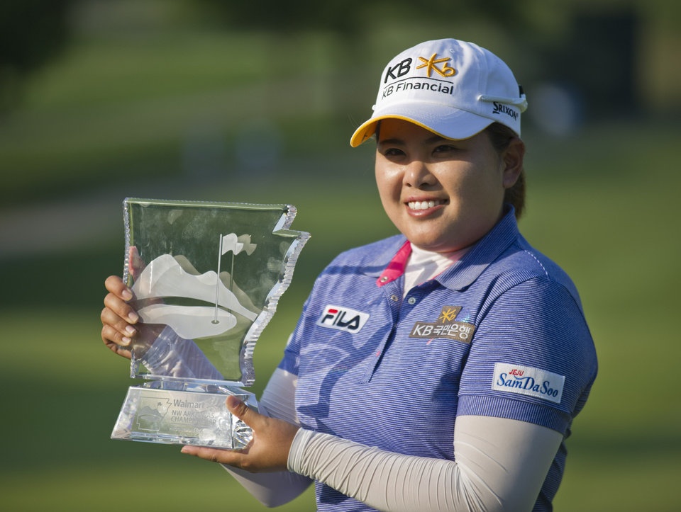 Inbee Park, of South Korea, holds the trophy on the 18th green following the final round of the LPGA NW Arkansas Championship golf tournament on Sunday, June 23, 2013, in Rogers, Ark. Park won the tournament in a playoff against compatriot So Yeon Ryu. (AP Photo/Beth Hall)