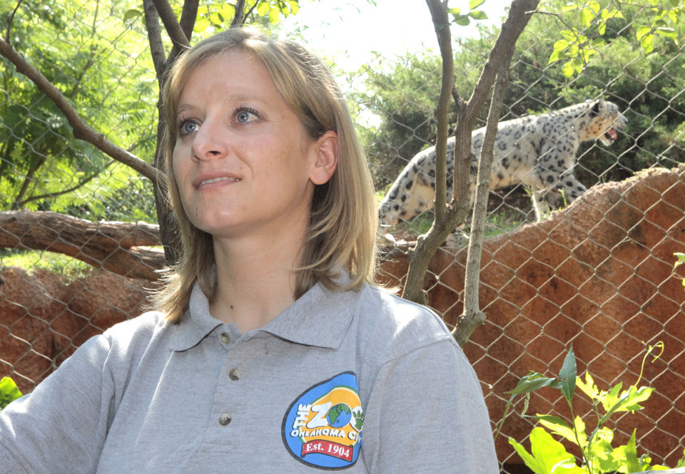 Photo - Jennifer D'Agostino, director of veterinary services at the Oklahoma City Zoo, recently talked about the Oklahoma weather and how the animals adjust to it. Dhirin, a snow leopard, is shown in the background.   David McDaniel - The Oklahoman
