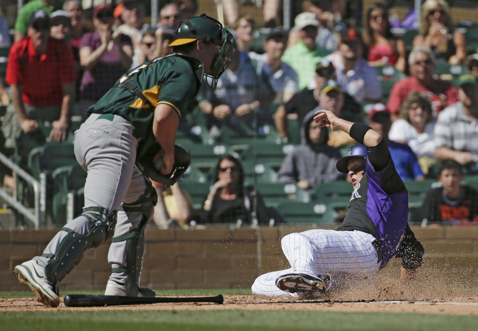 Photo - Colorado Rockies' Michael Cuddyer, right, scores on a double by Troy Tulowitzki past Oakland Athletics catcher John Jaso during the first inning of a spring training baseball game in Scottsdale, Ariz., Saturday, March 8, 2014. (AP Photo/Chris Carlson)