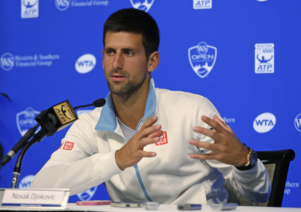 Photo - Novak Djokovic, from Serbia, answers questions during a news conference at the Western & Southern Open tennis tournament, Sunday, Aug. 10, 2014, in Mason, Ohio. Djokovic, the top seed, has been a finalist four times at the event, but has never won. (AP Photo/Al Behrman)
