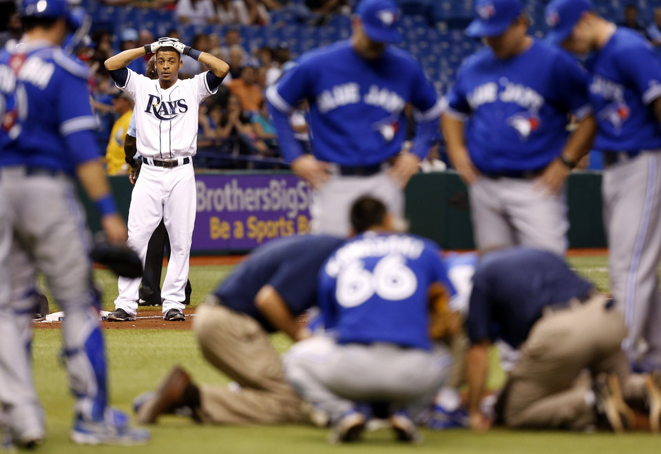 Tampa Bay Rays' Desmond Jennings reacts while medical personnel attend to Toronto Blue Jays starting pitcher J.A. Happ after during the second inning of a baseball game Tuesday, May 7, 2013, in St. Petersburg, Fla. Happ was hit by a line drive off of Jennings' bat. (AP Photo/Mike Carlson)