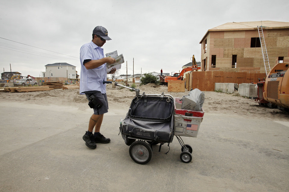 """Photo - FILE - In this Oct. 17, 2013 file photo, a postal carrier makes his rounds through Breezy Point, in the Queens borough of New York. The house on the right will replace one of the homes that burned to the ground during Superstorm Sandy in October 2013. Criticizing New York City's """"Build it Back"""" program as """"overly complex,"""" New York City Mayor Bill de Blasio announced on Thursday, April 17, 2014, reforms to the program meant to aid New Yorkers repairing damage left in the wake of Superstorm Sandy. (AP Photo/Mark Lennihan, File)"""