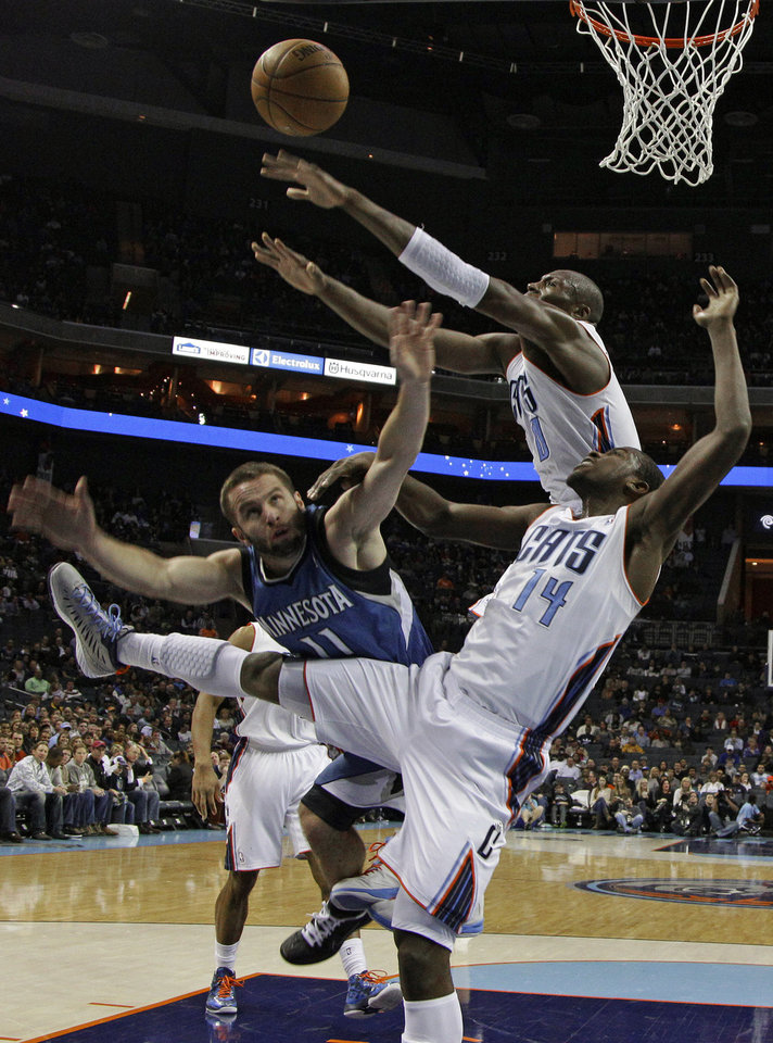 Minnesota Timberwolves' J.J. Barea (11) loses the ball as he drives between Charlotte Bobcats' Michael Kidd-Gilchrist (14) and Bismack Biyombo (0) during the first half of an NBA basketball game in Charlotte, N.C., Saturday, Jan. 26, 2013. (AP Photo/Chuck Burton)