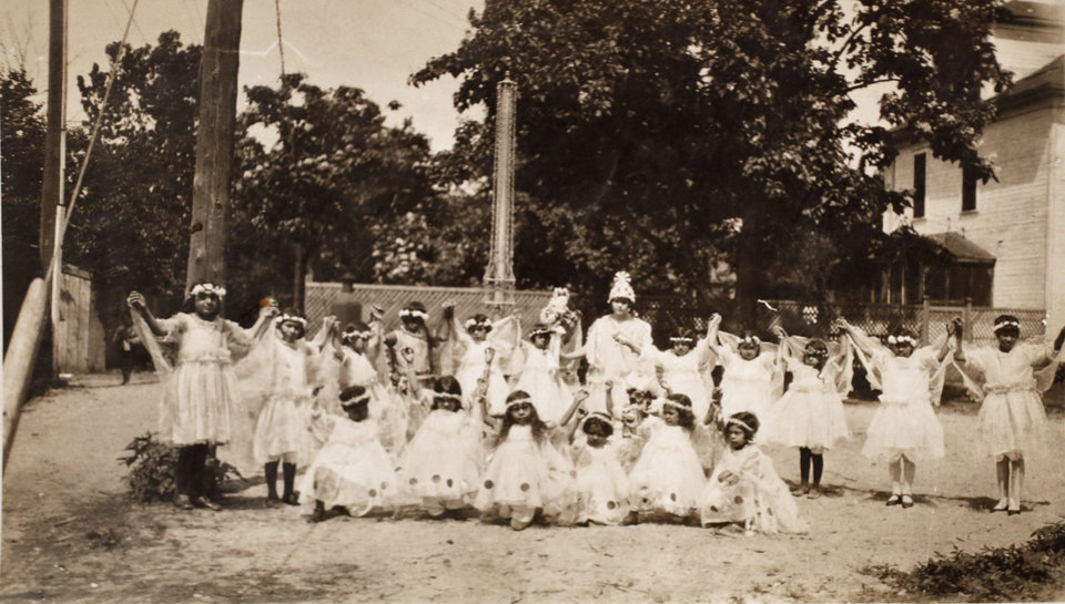 Photo - Latina students wearing matching white dresses dance as part of a play held for fun at Little Flower schoolhouse in the 1930s. Photo provided by Margarita Martinez