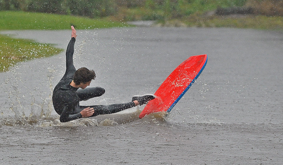 Photo - Ryan Springer, 16, surfs a large puddle off in Carpinteria, Calif., Saturday, March 1, 2014. The storm marked a sharp departure from many months of drought that has grown to crisis proportions for the state's vast farming industry. However, such storms would have to become common to make serious inroads against the drought, weather forecasters have said. (AP Photo/Santa Barbara News-Press, Mike Eliason)
