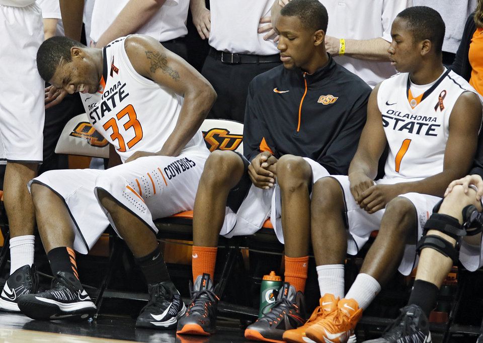 Photo - Oklahoma State 's Marcus Smart (33) goes to the bench with an injury after fouling out in the second overtime during the college basketball game between the Oklahoma State University Cowboys (OSU) and the University of Kanas Jayhawks (KU) at Gallagher-Iba Arena on Wednesday, Feb. 20, 2013, in Stillwater, Okla. Photo by Chris Landsberger, The Oklahoman