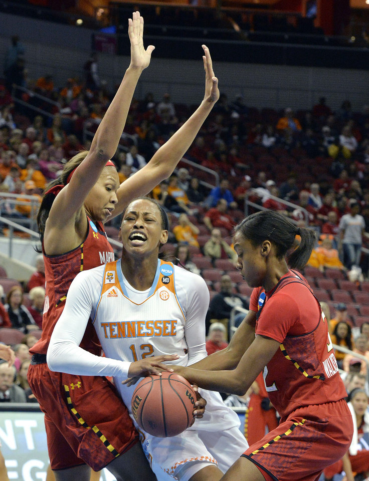 Photo - Tennessee's Bashaara Givens, center, fights her way through the defense of Maryland's Alicia Devaughn, left, and Shatori Walker Kimbrough during the first half in a regional semifinal game at the NCAA women's college basketball tournament, Sunday, March 30, 2014, in Louisville, Ky. (AP Photo/Timothy D. Easley)