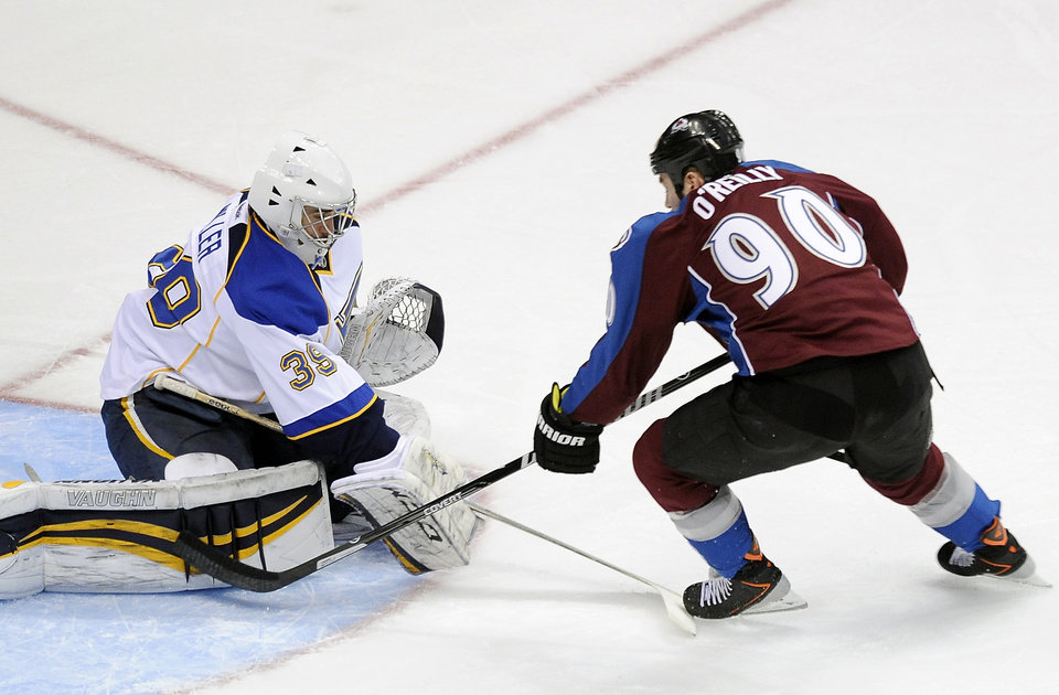 Photo - St. Louis Blues goalie Ryan Miller, left, stops a breakaway by Colorado Avalanche center Ryan O'Reilly, right, in the first period of an NHL hockey game on Saturday, March 8, 2014, in Denver. (AP Photo/Chris Schneider)