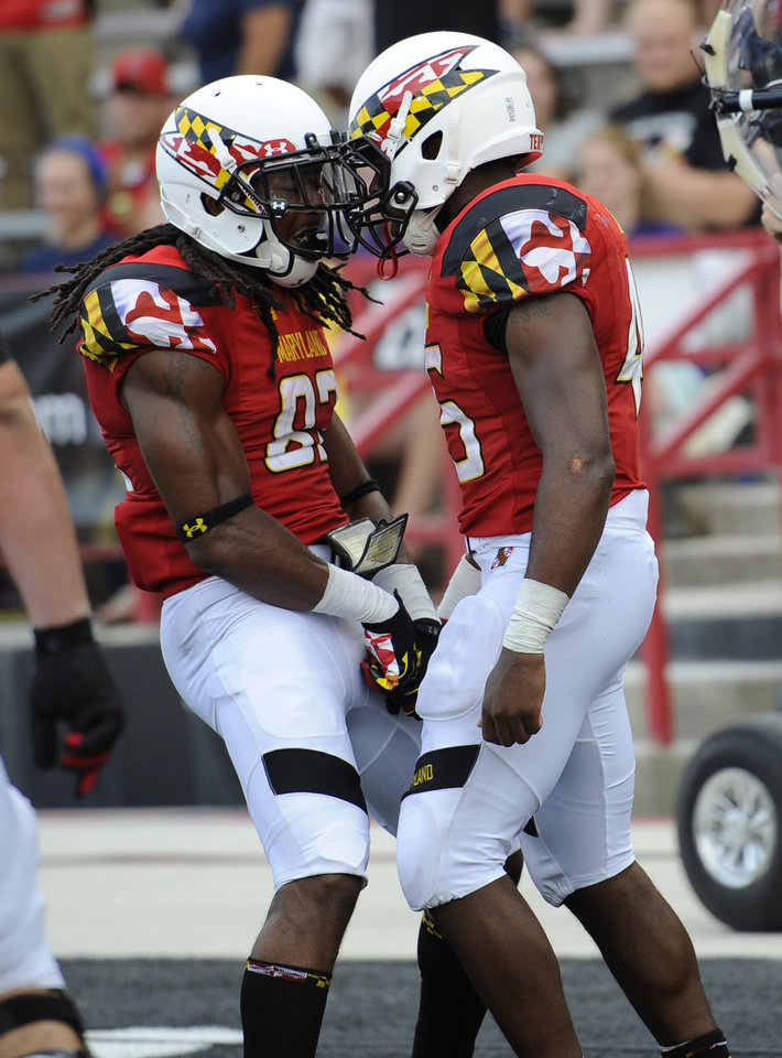 Photo - Maryland running back Brandon Ross, right, celebrates his touchdown with Marcus Leak, left, during the second half of an NCAA college football game against James Madison, Saturday, Aug. 30, 2014, in College Park, Md. Maryland won 52-7. (AP Photo/Nick Wass)