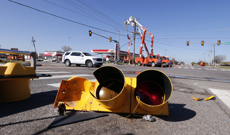 Photo - Workers replace power poles and traffic signals damaged by Wednesday's tornadoes at SW 119th and Western on Thursday, March 26, 2015 in Moore, Okla. Photo by Steve Sisney, The Oklahoman