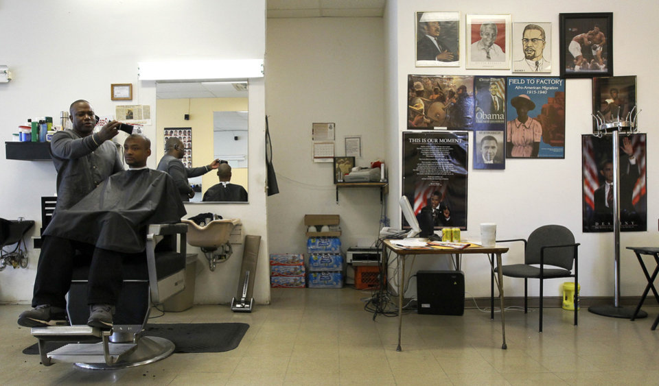 Photo -   Barber Bert Downing gives Kiel Sprawls a hair cut as they talk about their support of President Barack Obama and the election at Carter's Barbershop in Chicago on Election Day, Tuesday, Nov. 6, 2012. At right is a wall decorated with pictures of historical black leaders. The barber shop sits on the edge of a West Side ward that supported the president by a 99 percent-plus majority in 2008. And the regulars are pleased with his policies. (AP Photo/Charles Rex Arbogast)