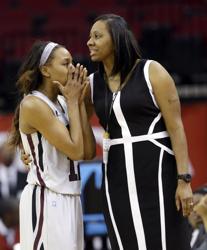 Photo - Texas Southern's Morgan Simmons, left, talks with her coach Johnetta Hayes-Perry after being called for technical foul during the closings minutes of the second half of an NCAA college basketball game against Prairie View A&M in the championship of the Southwestern Athletic Conference tournament Saturday, March 15, 2014, in Houston. Prairie View A&M won 63-58. (AP Photo/David J. Phillip)