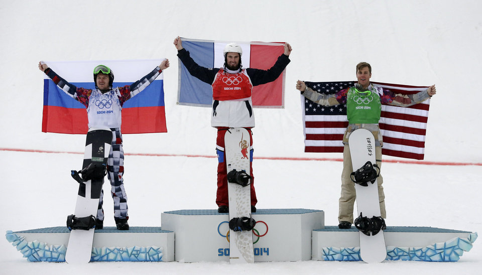 Photo - France's Pierre Vaultier, center, celebrates his gold medal with silver medalist Nikolai Olyunin of Russia, left, and bronze medalist Alex Deibold of the United States after the men's snowboard cross final at the Rosa Khutor Extreme Park, at the 2014 Winter Olympics, Tuesday, Feb. 18, 2014, in Krasnaya Polyana, Russia. (AP Photo/Andy Wong)