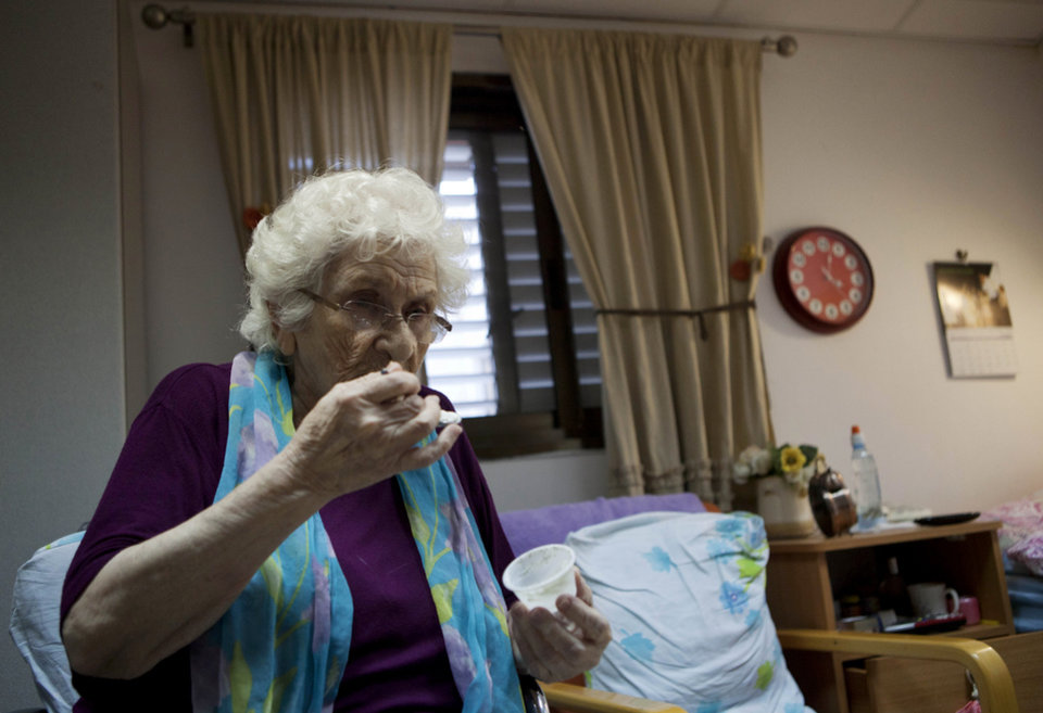 Photo -   In this photograph made on Tuesday, Oct. 30, 2012, Rivke Holop, 85, eats medical cannabis at the old age nursery home in kibbutz Naan next to the city of Rehovot, Israel. Marijuana is illegal in Israel but medical use has been permitted since the early nineties for cancer patients and those with pain-related illnesses such as Parkinson's, Multiple Sclerosis, and even post-traumatic stress disorder. (AP Photo/Dan Balilty)