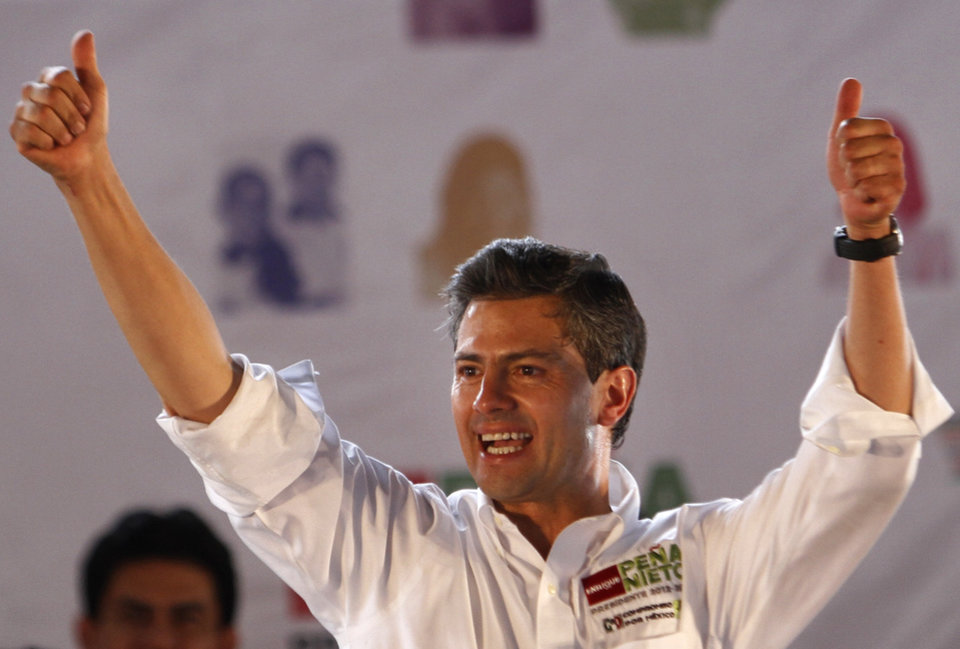 Photo -   In this April 28, 2012 photo, Enrique Pena Nieto, presidential candidate for the Institutional Revolutionary Party (PRI), greets supporters during a campaign rally in Nezahualcoyotl, Mexico. If the next two months go as Pena Nieto plans, the PRI will return to Mexico's highest office after 12 years out of power, thanks to the tightly disciplined and highly professional political machinery of a 45-year-old candidate who has managed to push questions about his personal flaws, and the details of his plans for Mexico, to the background. Mexico will hold presidential elections on July 1. (AP Photo/Marco Ugarte)
