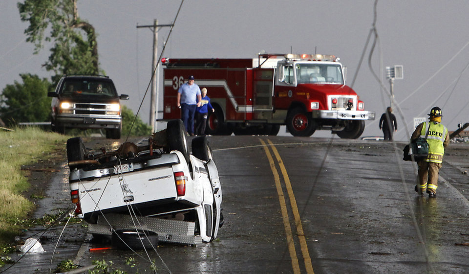 Photo - Power lines cross the road where a truck was flipped over after a tornado damaged the area around I-40 and Choctaw Road on Monday, May 10, 2010, in Oklahoma City, Okla.  Photo by Chris Landsberger, The Oklahoman