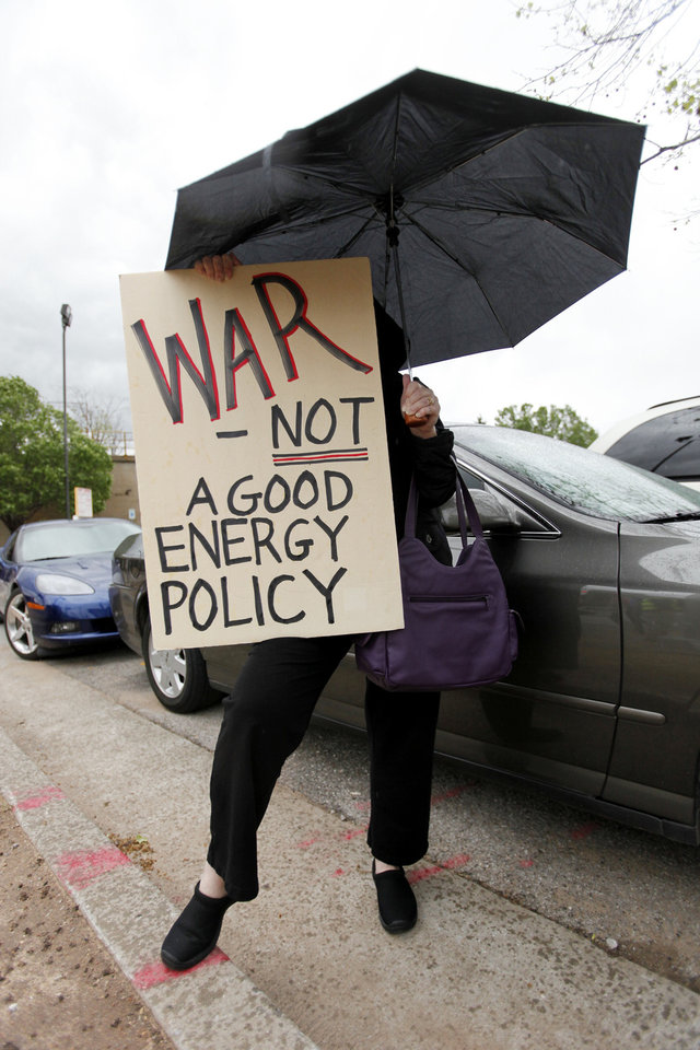 Photo - An unidentified person (did want to give name) holds a sign and an umbrella while taking part in a protest at Reno and E.K. Gaylord on the drive home Wednesday, March 21, 2012. Photo by Doug Hoke, The Oklahoman