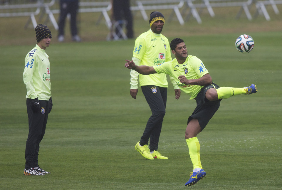 Photo - Brazil's Hulk controls the ball as Oscar, left, and Maicon, center back, watch during a practice session at the Granja Comary training center in Teresopolis, Brazil, Friday, July 11, 2014. Brazil will face the Netherlands in the World Cup third-place match Saturday. (AP Photo/Leo Correa)