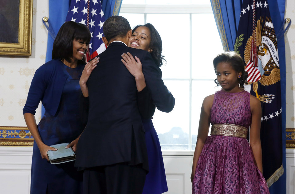 President Barack Obama hugs daughter Malia as first lady Michelle Obama and daughter Malia watch after Obama was officially sworn-in by Chief Justice John Roberts, not pictured, in the Blue Room of the White House during the 57th Presidential Inauguration in Washington, Sunday, Jan. 20, 2013.  (AP Photo/Larry Downing, Pool) ORG XMIT: WX311
