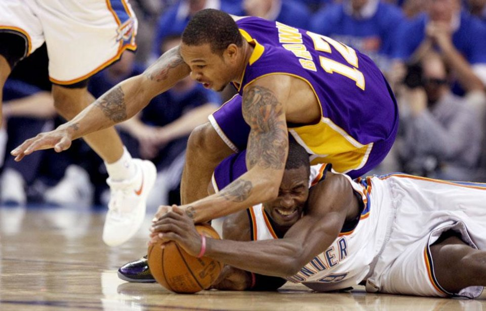 NBA PLAYOFFS / L.A. LAKERS: Oklahoma City\'s Serge Ibaka (9) fights LA.\'s Shannon Brown (12) for a loose ball during the NBA basketball game between the Los Angeles Lakers and the Oklahoma City Thunder in game six of the first round series at the Ford Center in Oklahoma City, Friday, April 30, 2010. Photo by Sarah Phipps, The Oklahoman ORG XMIT: KOD