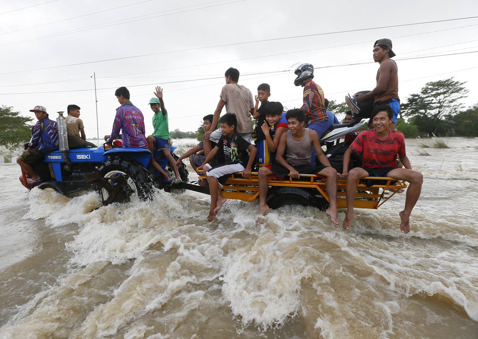 Photo - Commuters ride a farm tractor as it maneuvers through strong floodwaters from Typhoon Koppu along a highway in La Paz township, Tarlac province, northern Philippines Tuesday, Oct. 20, 2015. Slow-moving Typhoon Koppu blew ashore with fierce winds in the northeastern Philippines early Sunday, toppling trees and knocking out power and communications and forcing the evacuation of thousands of villagers. (AP Photo/Bullit Marquez)