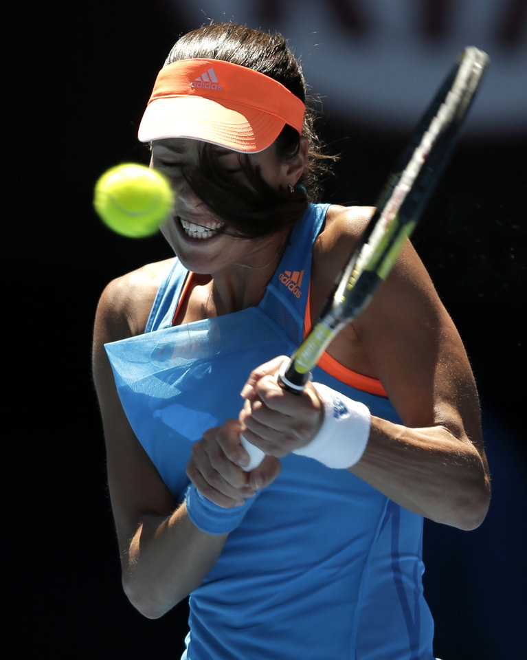 Photo - Ana Ivanovic of Serbia makes a backhand return to Eugenie Bouchard of Canada during their quarterfinal at the Australian Open tennis championship in Melbourne, Australia, Tuesday, Jan. 21, 2014.(AP Photo/Rick Rycroft)