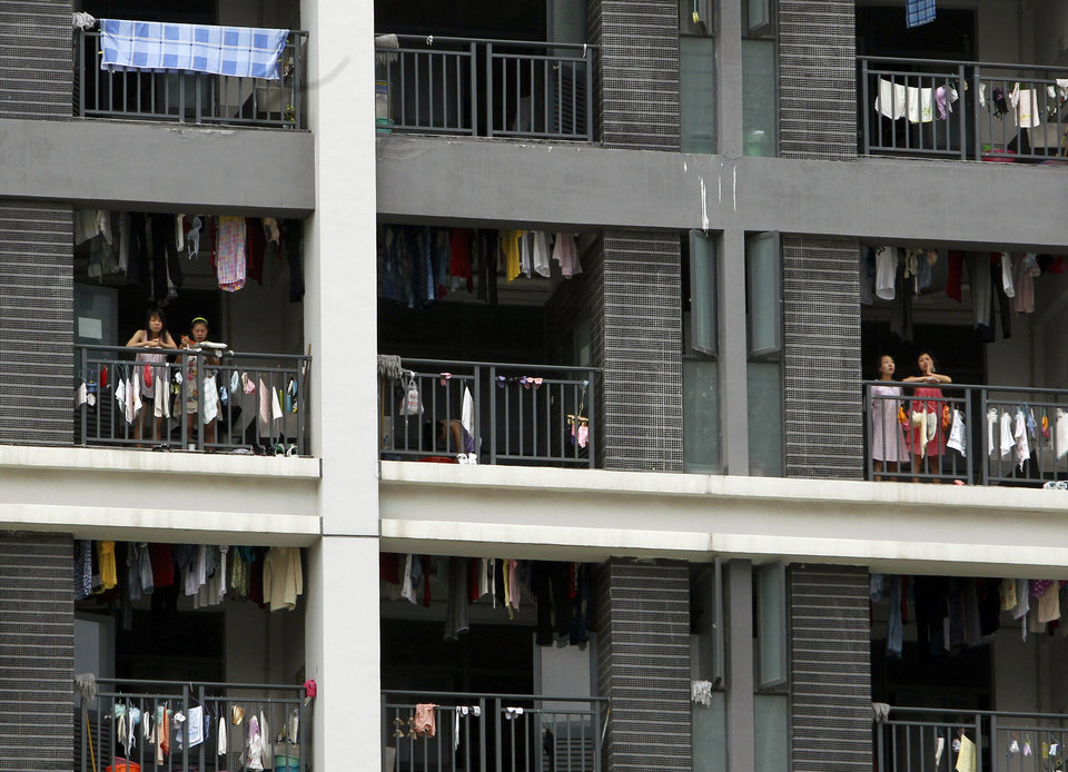 Photo -   FILE-In this Wednesday, May 26, 2010, file photo, employees stand on the balconies of a residential house at the Foxconn complex in Shenzhen, China. Foxconn, the company that makes Apple's iPhones suspended production at a factory in China on Monday, Sept. 24, 2012, after a brawl by as many as 2,000 employees at a dormitory injured 40 people. The fight, the cause of which was under investigation, erupted Sunday night at a privately managed dormitory near a Foxconn Technology Group factory in the northern city of Taiyuan, the company and Chinese police said. (AP Photo/Kin Cheung, File)