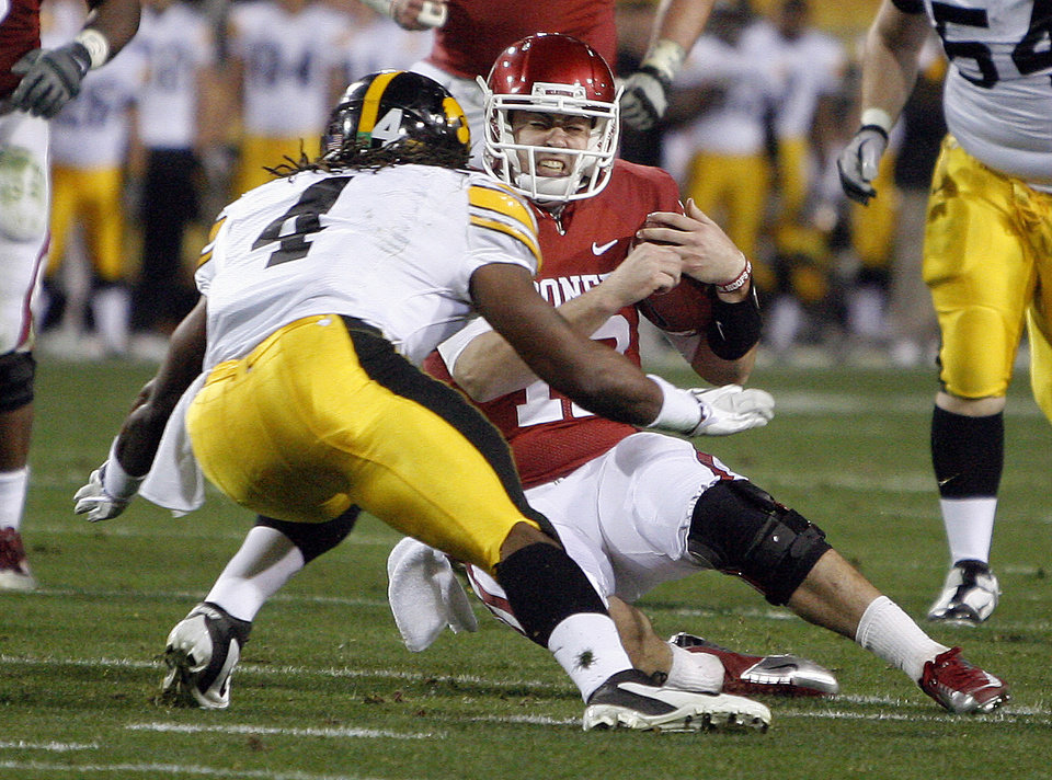 Oklahoma's Landry Jones (12) is tackled by Iowa's Jordan Bernstine (4)  during the Insight Bowl college football game between the University of Oklahoma (OU) Sooners and the Iowa Hawkeyes at Sun Devil Stadium in Tempe, Ariz., Friday, Dec. 30, 2011. Photo by Sarah Phipps, The Oklahoman