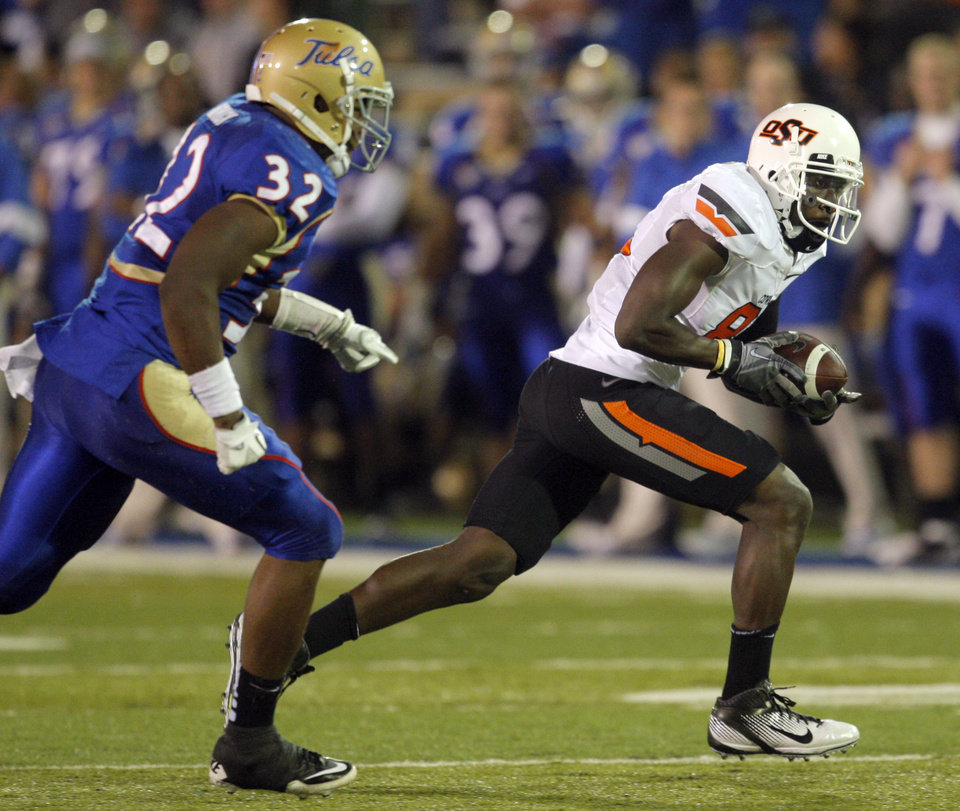 Photo - Oklahoma State's Justin Blackmon (81) runs past Tulsa's Curnelius Arnick (32)during the third quarter of the college football game between the Oklahoma State University Cowboys and the University of Tulsa Golden Hurricane at H.A. Chapman Stadium in Tulsa, Okla., Sunday, Sept. 18, 2011. Photo by Sarah Phipps, The Oklahoman