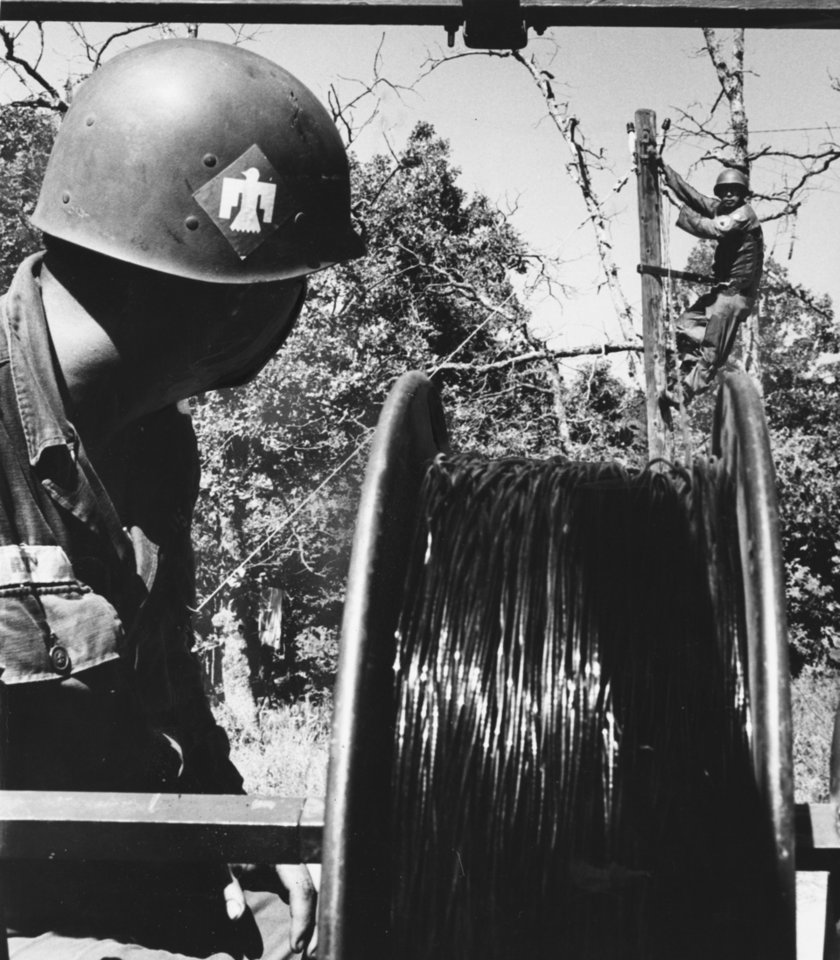 Photo - JANGLING TELEPHONES weren't left behind when Oklahoma's 45th Infantry Division Thunderbirds went to Fort Chaffee, Ark., for their annual summer camp.  Here Sgt. John Goat, 4028 SW 25, Oklahoma City, on pole, and Pvt. Jimmie Reed, Sapulpa, string wire for field phones so 45th units scattered for miles can talk to each other.  Staff photo by George Tapscott.  Staff photo dated 08/06/1963 and published on 08/07/1963 in The Oklahoma City Times.