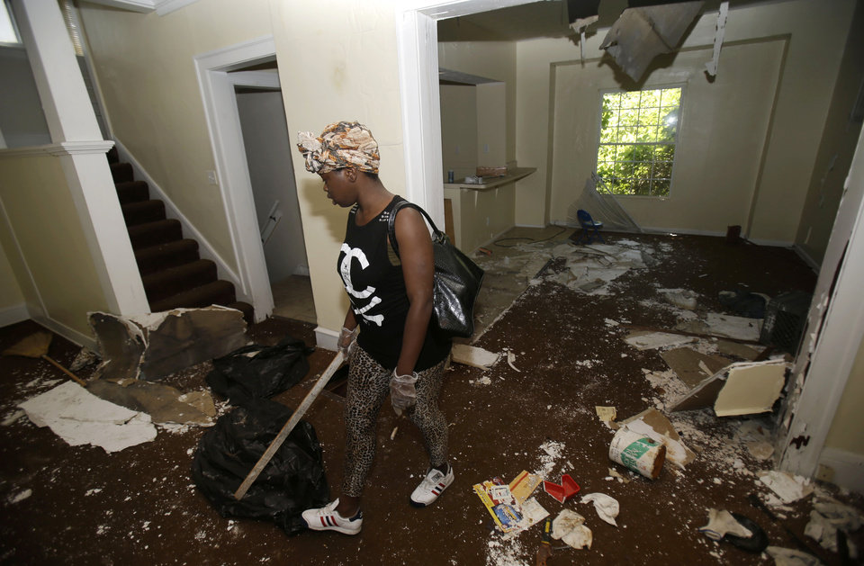 Photo - Sanautica Hicks-Ross, 18, searches an abandoned home Sunday, July 21, 2013, near where three bodies were found in East Cleveland, Ohio. Hicks-Ross is an East Cleveland resident. Police Chief Ralph Spotts told volunteers checking vacant houses in a neighborhood where three bodies were found wrapped in plastic bags that he believes there could be one or two more victims. (AP Photo/Tony Dejak)