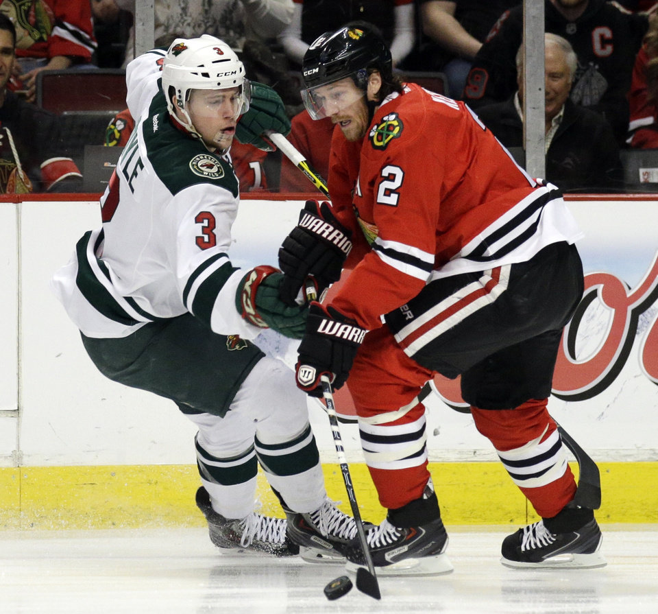 Photo - Chicago Blackhawks' Duncan Keith (2), right, controls the puck against Minnesota Wild's Charlie Coyle (3)  during the first period  in Game 2 of an NHL hockey second-round playoff series in Chicago, Sunday, May 4, 2014. (AP Photo/Nam Y. Huh)