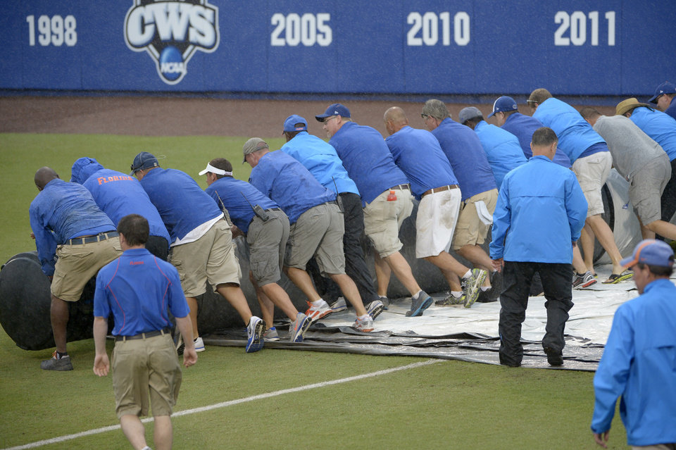 Photo - Members of the grounds crew roll out the tarp as a second rain delay is called during the seventh inning of an NCAA college baseball regional tournament game between Long Beach State and North Carolina in Gainesville, Fla., Sunday, June 1, 2014.(AP Photo/Phelan M. Ebenhack)