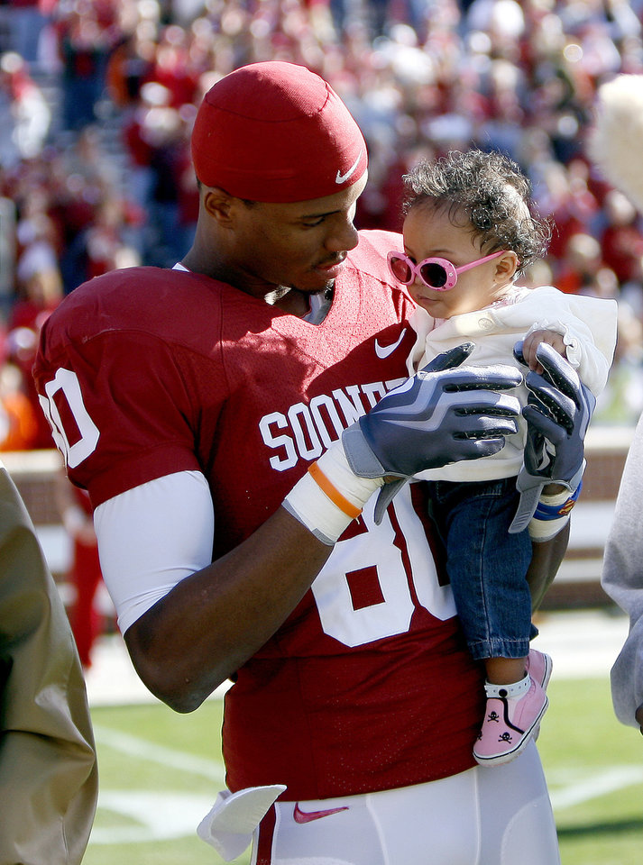 Photo - OU's Adron Tennel holds his daughter, Ava, during senior day activities before the Bedlam college football game between the University of Oklahoma Sooners (OU) and the Oklahoma State University Cowboys (OSU) at the Gaylord Family-Oklahoma Memorial Stadium on Saturday, Nov. 28, 2009, in Norman, Okla. Photo by Sarah Phipps, The Oklahoman