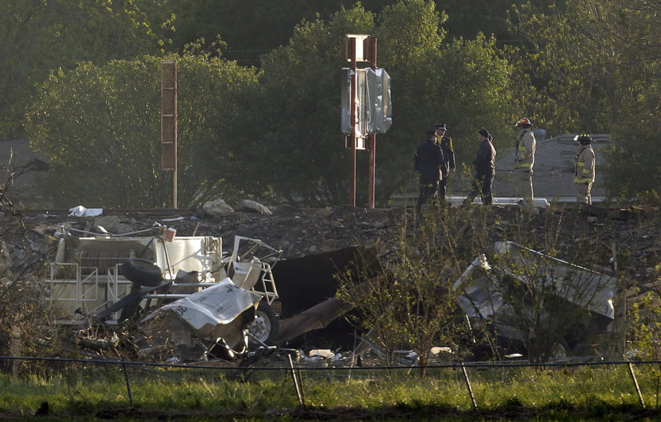 Photo - Workers walk among debris Thursday, April 18, 2013, a day after an explosion at a fertilizer plant in West, Texas. The massive explosion at the West Fertilizer Co. Wednesday night killed as many as 15 people and injured more than 160. (AP Photo/Charlie Riedel)