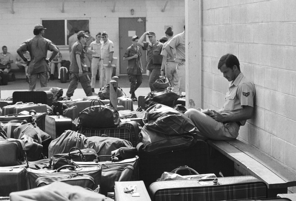 In this March 27, 1973 photo, surrounded by luggage of other departing GIs, U.S. Air Force airman reads paperback novel as he waits to begin processing at Camp Alpha on Saigon's Tan Son Nhut airbase in Saigon as troop withdrawals resume after 10 day-delay. More than 900 will leave with all U.S. troops out by Thursday. As the last U.S. combat troops left Vietnam 40 years ago, angry protesters still awaited them at home. North Vietnamese soldiers took heart from their foes' departure, and South Vietnamese who had helped the Americans feared for the future. While the fall of Saigon two years later � with its indelible images of frantic helicopter evacuations � is remembered as the final day of the Vietnam War, Friday marks an anniversary that holds greater meaning for many who fought, protested or otherwise lived it. (AP photo/Charles Harrity)