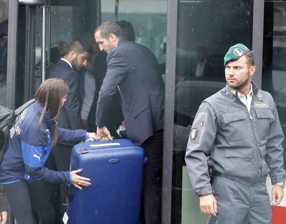 Photo - Italy players Giorgio Chiellini, center, is helped with his luggage upon his arrival with teammates at Malpensa airport after landing from Brazil, in Milan, Italy, Thursday, June 26, 2014. Italy was disqualified from the World Cup after loosing to Uruguay in their group stage round.  (AP Photo/Luca Bruno)