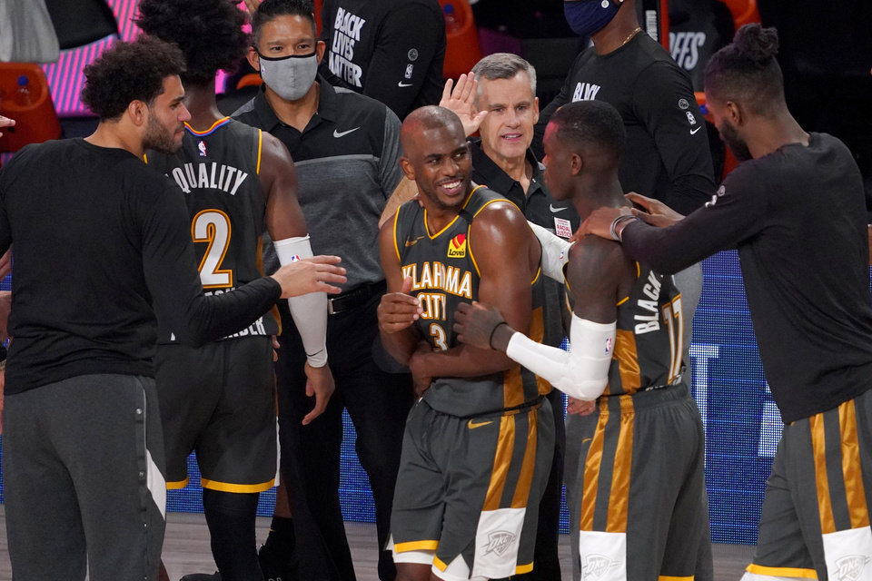 Photo - Oklahoma City Thunder's Chris Paul (3), Dennis Schroder (17), head coach Billy Donovan, center rear, and others celebrate their 104-100 win against the Houston Rockets in an NBA first-round playoff basketball game, Monday, Aug. 31, 2020, in Lake Buena Vista, Fla. (AP Photo/Mark J. Terrill)
