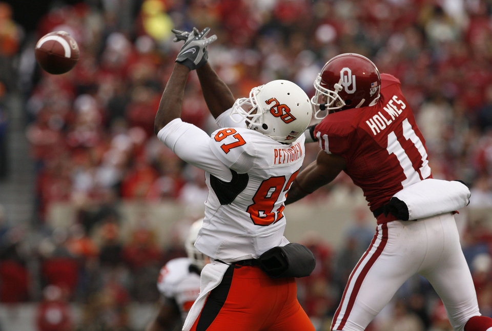 Photo - Lendy Holmes (11) breaks up a pass intended for Brandon Pettigrew (87)during the first half of the college football game between the University of Oklahoma Sooners (OU) and the Oklahoma State University Cowboys (OSU) at the Gaylord Family-Memorial Stadium on Saturday, Nov. 24, 2007, in Norman, Okla. 